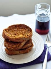 Easy french toast on a white plate next to a glass of maple syrup.