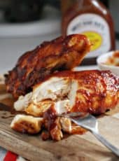 Oven Baked BBQ Chicken being cut on cutting board