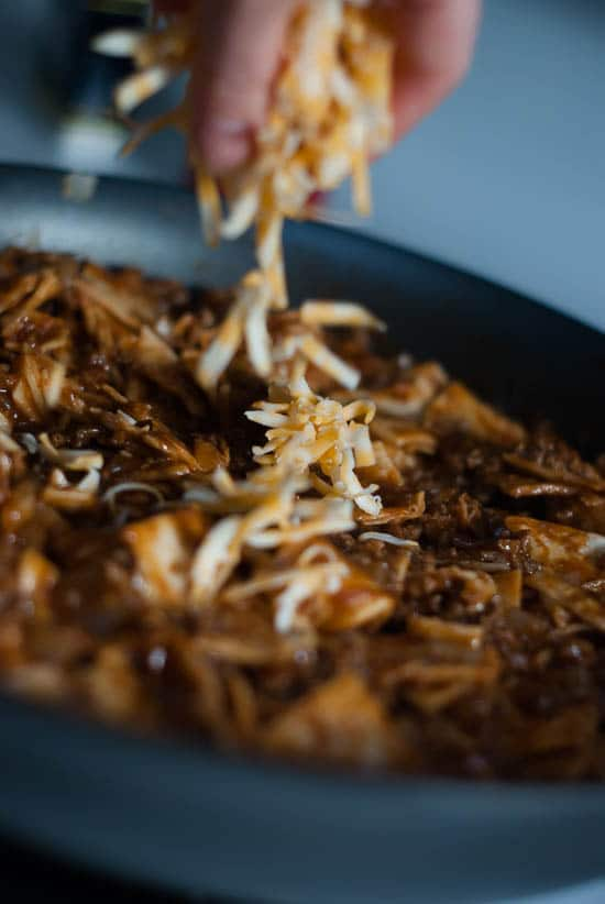 Sprinkling colby jack cheese over homemade Beef Enchilada recipe in a skillet.