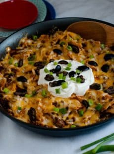 From scratch Beef Enchilada Skillet topped with fresh olives and green onions.