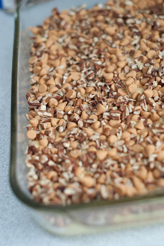 Butterscotch chips and pecans over simple hornet's nest cake mix in a clear cake pan.