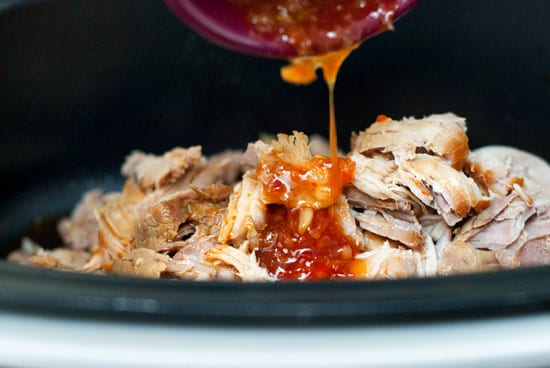 Pouring sweet chili sauce over pulled pork in a slow cooker.