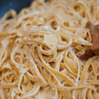 Mixing from scratch fettuccine Alfredo noodles in a large skillet.