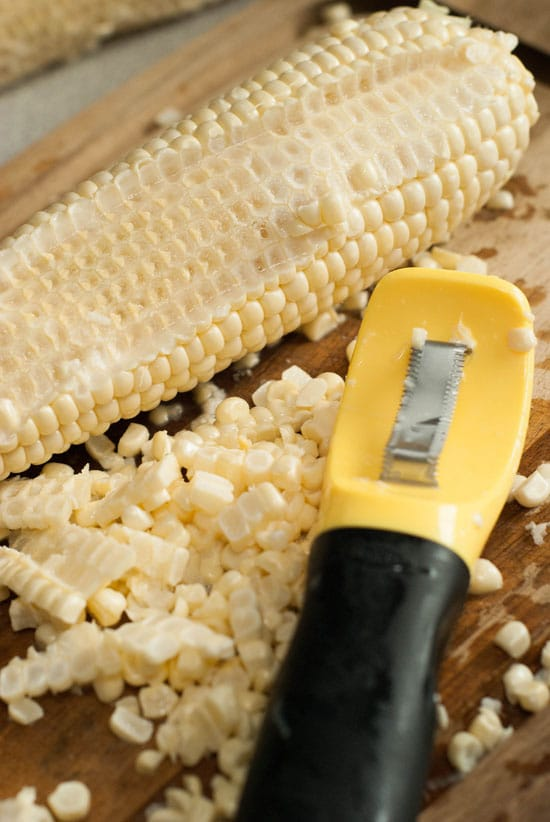 OXO Corn peeler and freshly cut corn on a wooden board.