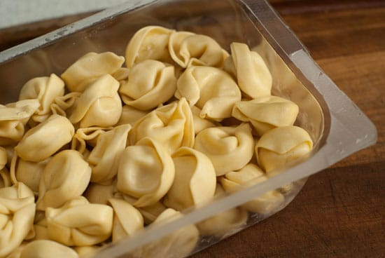 Frozen tortellini pasta in a clear container on a wooden table.