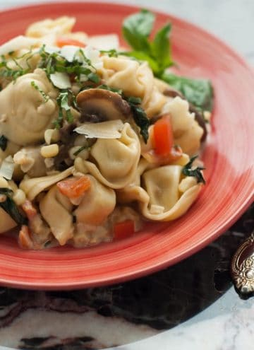From scratch Tortellini Primavera on a red plate on a table.
