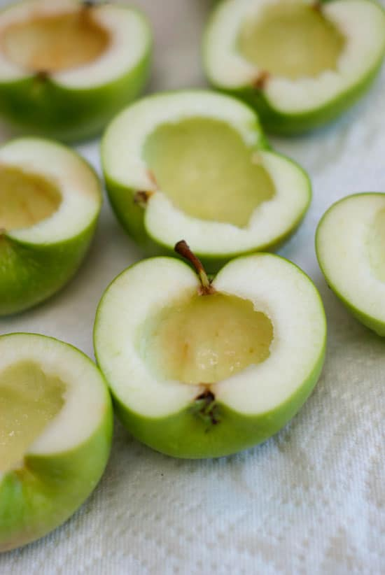 Core missing out of sliced green apples on a napkin.
