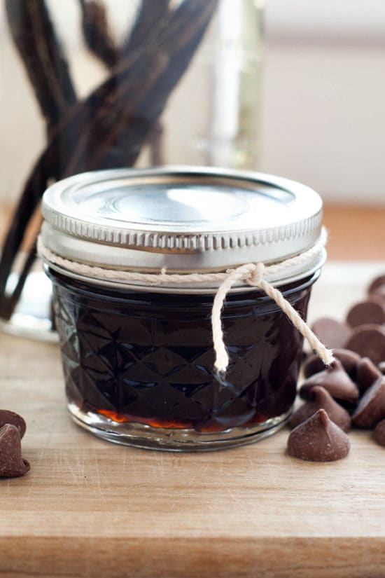 Delicious Vanilla Extract in a small glass jar surrounded by chocolate chips on a wooden table.