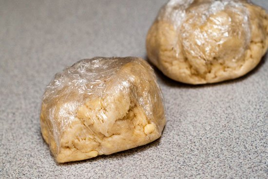 Easy pie crust dough rolled into balls in plastic wrap.