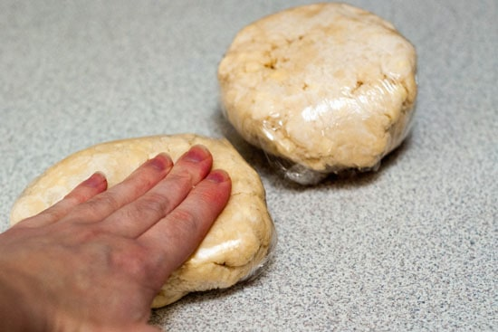 Pressing pie crust ingredients in plastic wrap into flat disks.