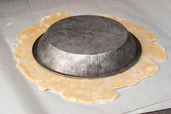 Silver pie pan on top of simple pie crust dough.