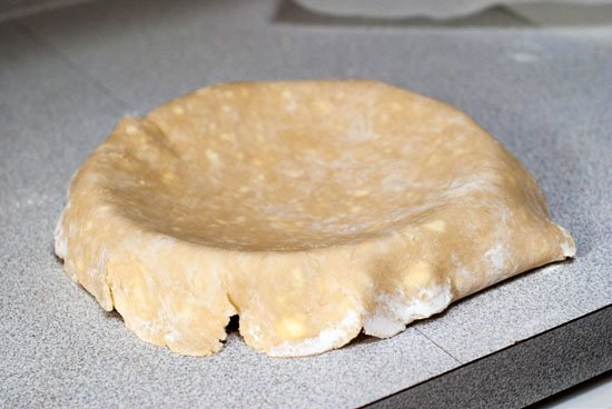 No Fail pie crust dough on top of pie dish on a table.