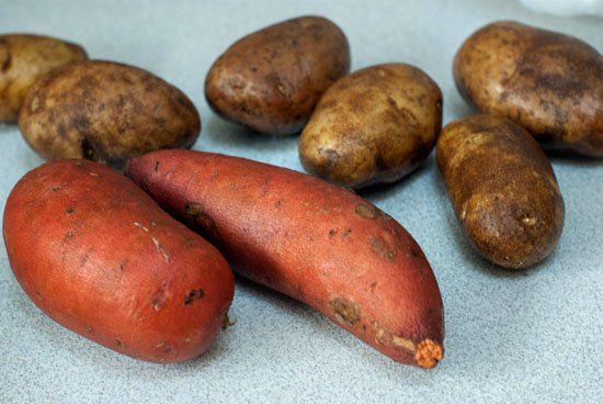 russet potatoes and sweet potatoes on a table.