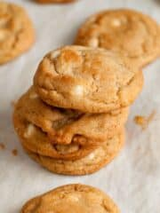 Stacked easy white chocolate chip macadamia nut cookies on parchment paper.