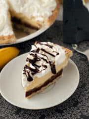 Easy Banana Cream Pie drizzled with chocolate and whipped cream in a small white plate.
