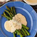 Asparagus drizzled with this Basic Cheese Sauce on a large blue plate.