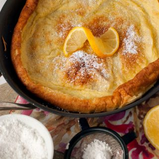 Easy Dutch Baby Pancakes recipe in a large black skillet with powdered sugar and sliced orange.