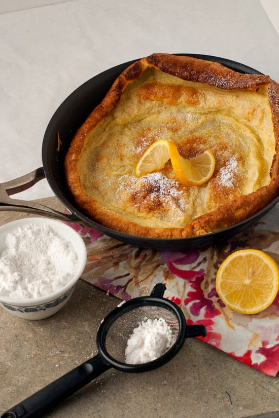 Puffy dutch baby pancake in a skillet next to a strainer with powdered sugar.