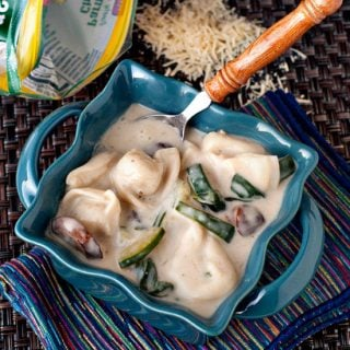 Tortellini Alfredo Soup with fresh parmesan in a small blue casserole dish.