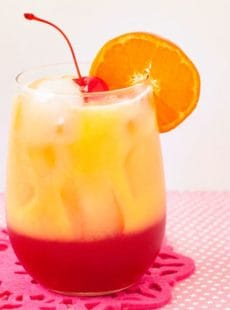 Non alcoholic drink in a drinking glass with fresh oranges and cherries.