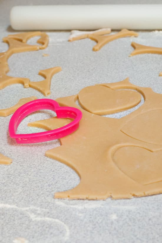 Pink heart shaped cookie cutter on sour cream sugar cookie dough.