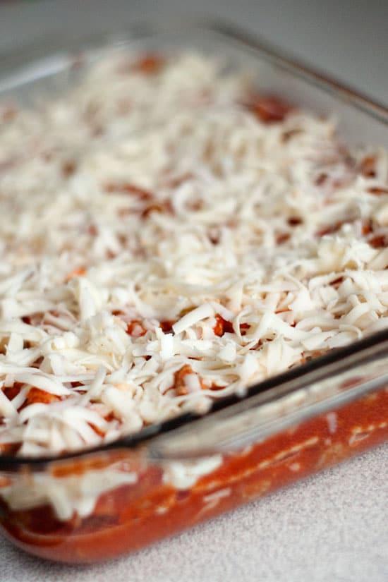 Shredded cheese on delicious Ravioli Lasagna in a glass casserole dish.