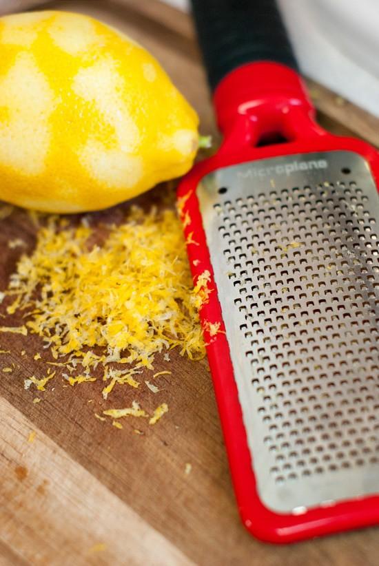 Zesting lemon on a wooden board.
