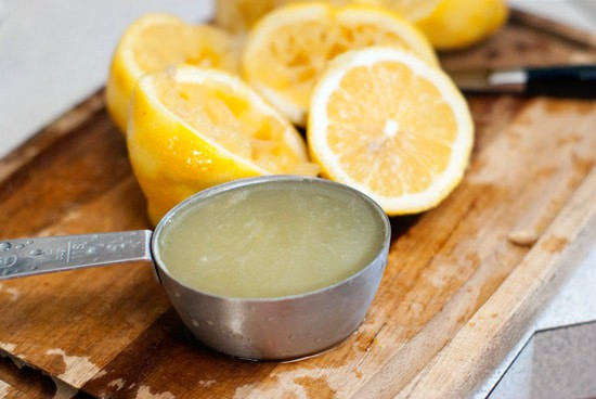 Lemon juice in a measuring spoon next to sliced lemons on a wooden cutting board.