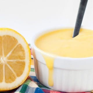 Fast Lemon Curd recipe in a small white bowl next to a half of a lemon.