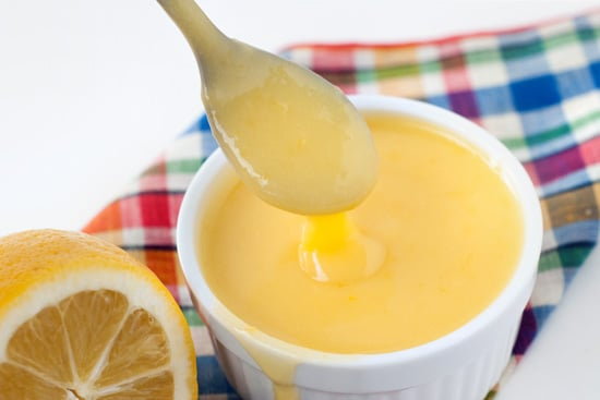 Tangy Lemon Curd recipe in a small white bowl with a metal spoon and sliced lemon.