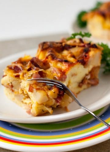 Easy Breakfast Strata slices on a small white plate with a silver fork.