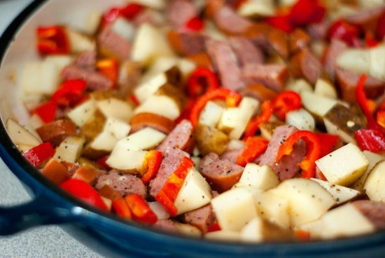 Potatoes, a bell pepper, onion, and some smoked sausage in a large skillet.