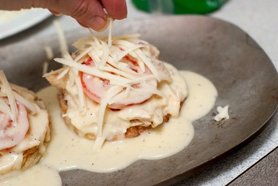 Adding fresh Monterrey Jack cheese over delicious Kentucky Hot Browns with sauce.