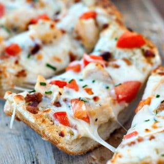 Simple Garlic Bread Pizza with mozzarella and tomatoes on a wooden board.