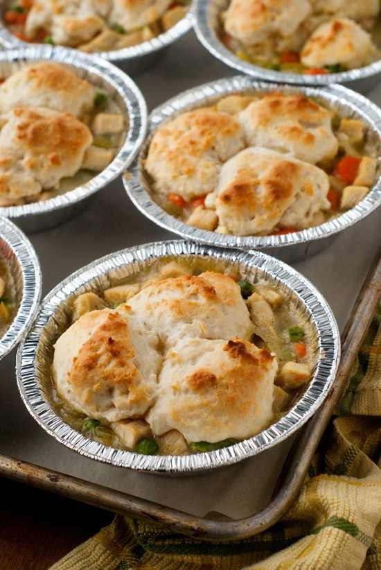 Easy Chicken Pot Pies in a baking sheet with peas and carrots.