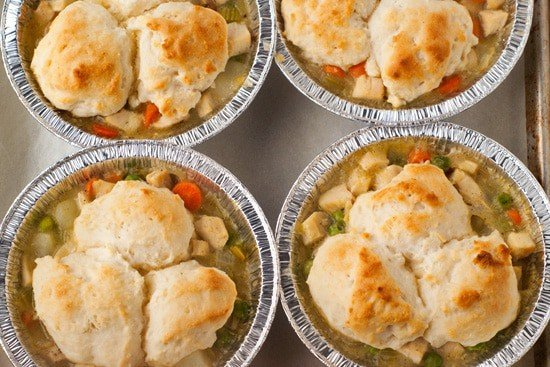Four simple Chicken Pot Pies in a baking sheet with gravy, biscuits, carrots and peas.