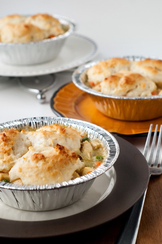 Three delicious Chicken Pot Pies with biscuits and gravy on serving plates.