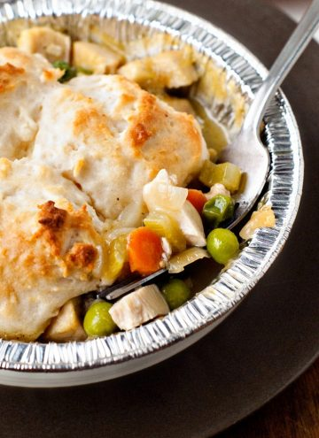 Biscuit Topped Chicken Pot Pie with gravy in a pie tin with a silver fork.