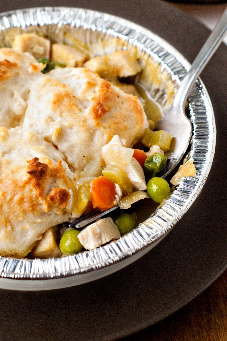 Delicious Biscuit Topped Chicken Pot Pie in a foil pie tin with a silver fork inside.
