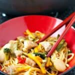 Simple Chicken Lo mein recipe in a black and red serving bowl with red chopsticks.