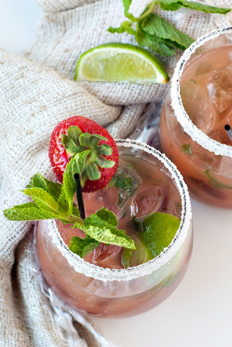 Two non alcoholic Strawberry Mojitos rimmed with salt and topped with fresh mint, strawberries and lime.