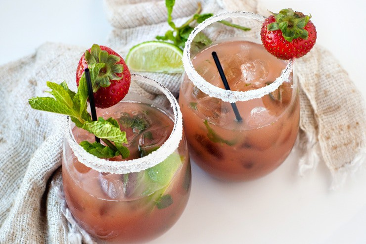 Two easy Strawberry Mojito Mocktails with mint, strawberries and sliced limes.