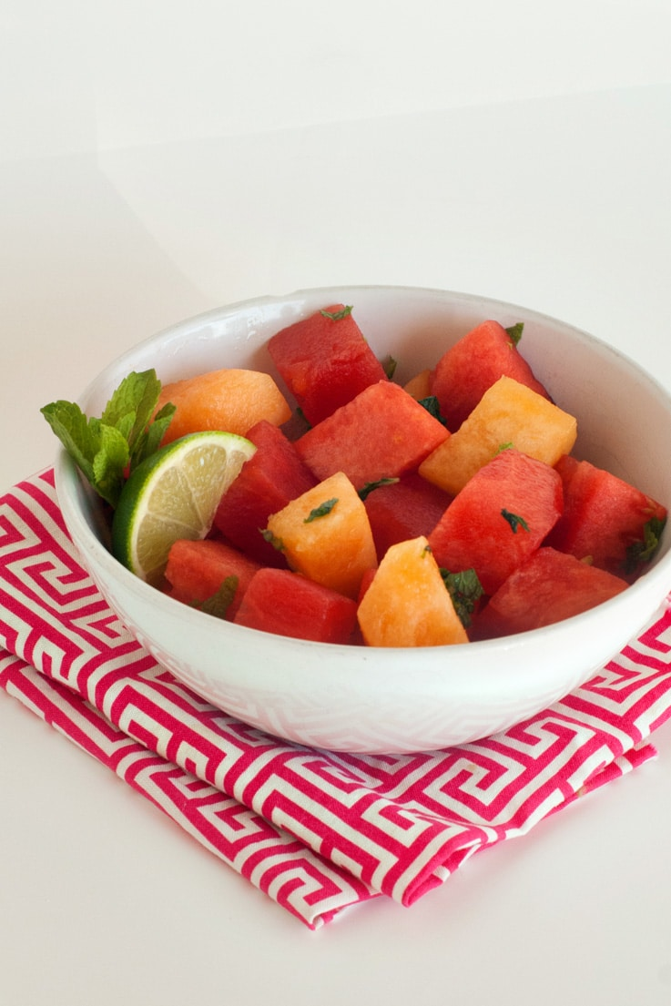 Simple Summer fruit bowl in a small white bowl with sliced lime, fresh mint, cantaloupe and watermelon.