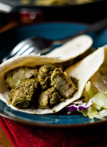 Healthy Cilantro Pesto Chicken in a warm tortilla on a blue plate with a silver fork.