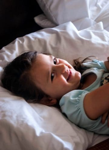 Girl laying on white pillow.