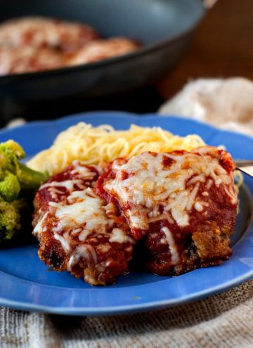 Beef Parmesan recipe in a blue plate with spaghetti noodles and broccoli.