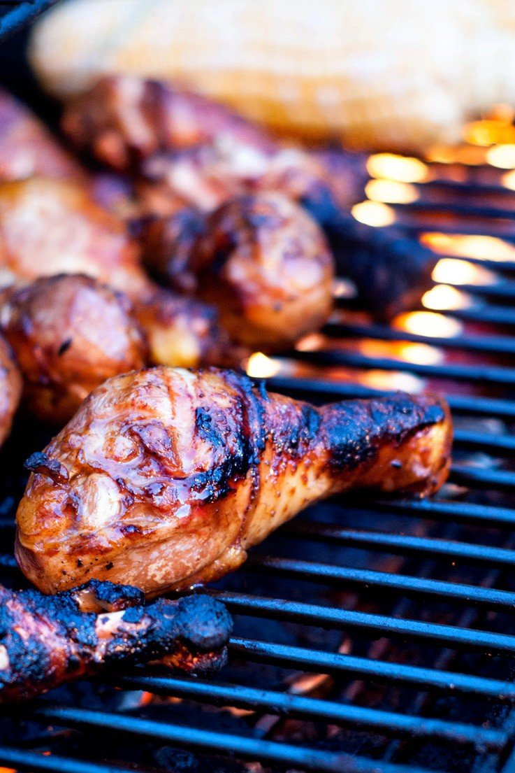Grilling chicken wings and drumsticks on a grill.