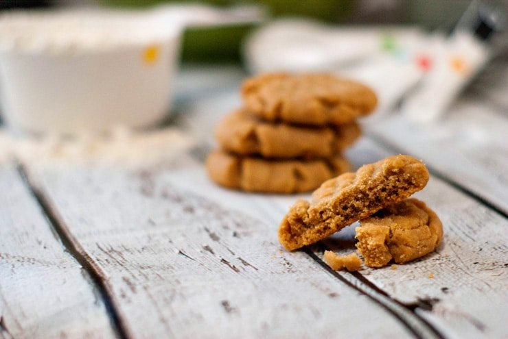 Five simple Peanut Butter Cookies on a wooden table.
