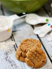 Easy Peanut Butter Cookies recipe on a wooden table next to measuring spoons.