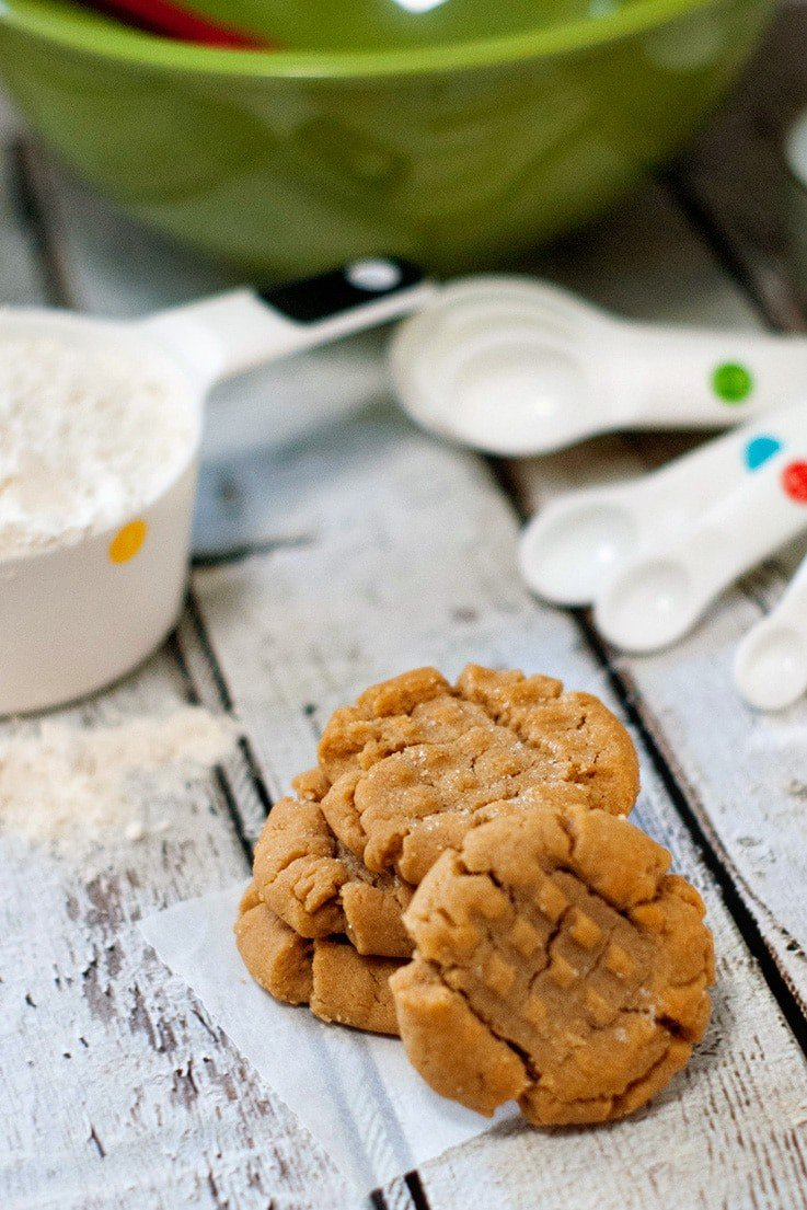 Three delicious Peanut Butter Cookies next to measuring spoons on a wooden table.